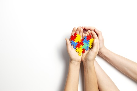 Mains tenant coeur coloré sur fond blanc. Concept de la journée mondiale de sensibilisation à l'autisme Banque d'images