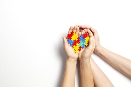 Manos sosteniendo corazón colorido sobre fondo blanco. Concepto del día mundial de la concienciación sobre el autismo Foto de archivo