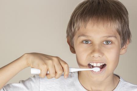 Kid brushing teeth with white electric toothbrush