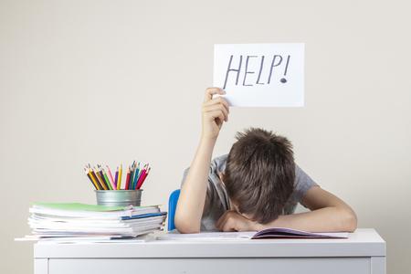 悲しい疲れた欲求不満の少年は、多くの本を持ってテーブルに座って、単語ヘルプで紙を持っています。学習困難、教育コンセプト。