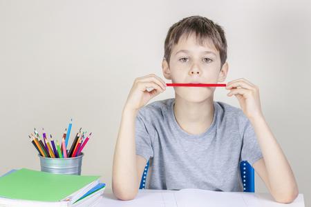 Niño haciendo la tarea en la mesa y pensando o soñando Foto de archivo