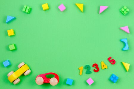 Baby kid toy background. Colorful wooden cubes, cars and numbers on green background 写真素材