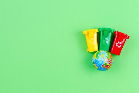 Problema di ecologia del pianeta inquinamento ambientale, consumismo, concetto di riciclaggio. Mini contenitori per cestini con globo su sfondo verde