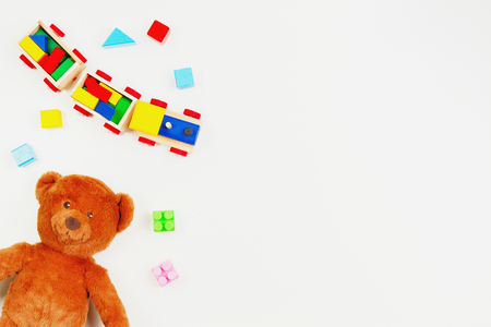 Baby kids toys background. Teddy bear, wooden train, colorful bricks on white table