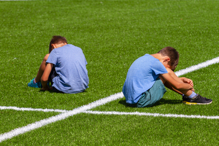 education, bullying, conflict, social relations and people concept - two sad disappointed boys sitting back to back on the grass in stadium Standard-Bild - 123008957