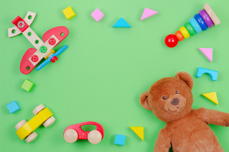Kids toys background frame with teddy bear, wooden plane, cars, baby stacking rings pyramid and colorful blocks on green background