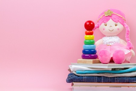 Donation, charity concept. Stuffed soft doll, baby stacking rings pyramid, kid clothes and books over pink background Imagens