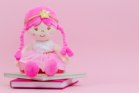 Stuffed soft doll sitting on the books over pink background