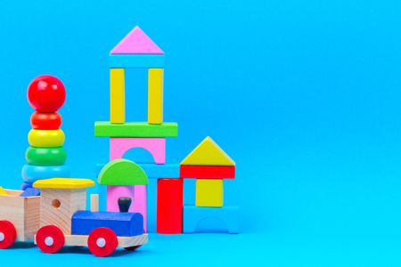 Baby kid toy background. Wooden toy train, baby stacking rings pyramid and colorful blocks on blue background Imagens