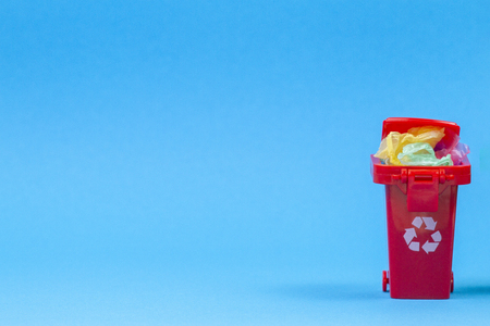 Red recycle bins container with plastic garbage on blue background
