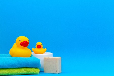Baby accessories for bath with yellow rubber ducks on blue background