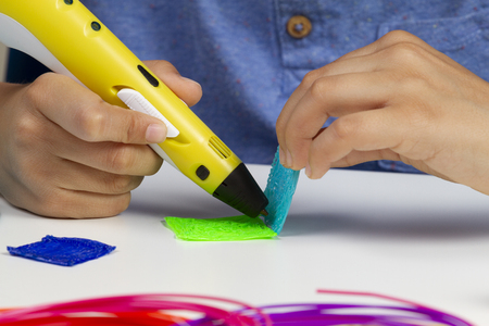 Kid hands creating with 3d printing pen new item