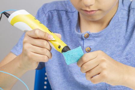 Boy creating with 3d printing pen new item Banco de Imagens