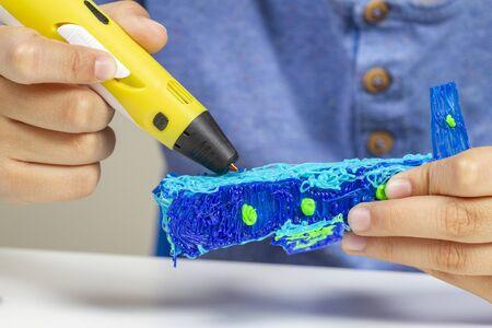 Boy hands creating with 3d pen blue plane. Banco de Imagens