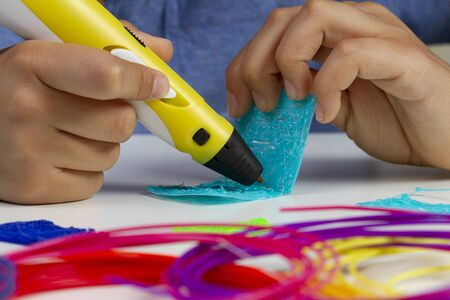 Kid hands with 3d printing pen creating new item