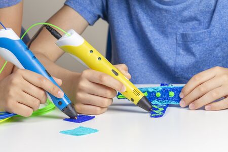 Kids hands creating with 3d printing pens