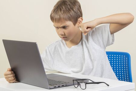 Angry young boy want to hit laptop computer