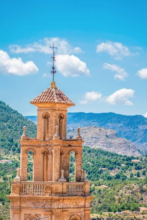 Panorama of Finestrat with Church of Saint Bartholomew and old bell tower and mountains background. Costa Blanca, Spain