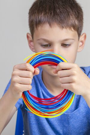 Kid holding colorful filaments for 3d pen and choose color for new item