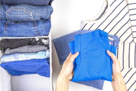 Frauenhände, die Kinderkleidung im Korb aufräumen. Vertikale Lagerung von Kleidung, Aufräumen, Raumreinigungskonzept Standard-Bild