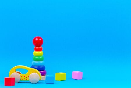 Baby kid toy background. Wooden toy train, baby stacking rings pyramid and colorful blocks on blue background 版權商用圖片 - 128769976