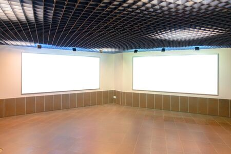 Mock up. Two big blank white billboards on the wall inside building 写真素材