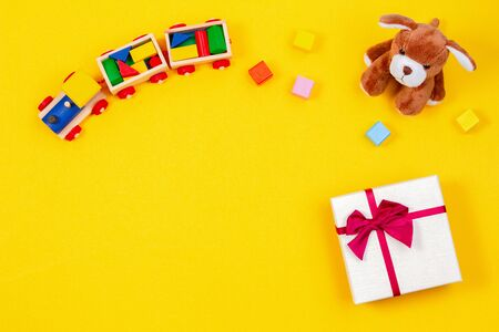 Kids baby toy background. Wooden train, stuffed puppy and present gift box on yellow background