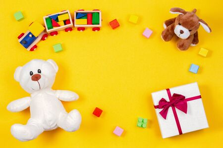Kids baby toy background. Teddy bear, toy train, present gift box and other toys on yellow background 写真素材