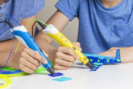 Two kid hands creating with 3d printing pens