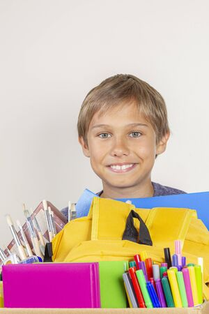 Donation concept. Kid holding donate box with books, pencils and school supplies Banco de Imagens