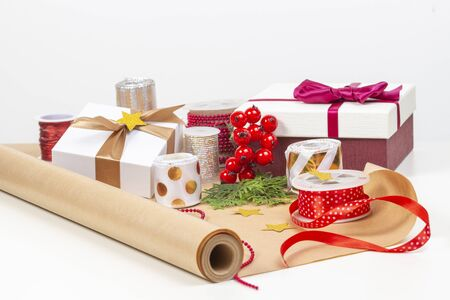 Christmas background with gifts present box, wrapping paper, ribbons, bows on white table