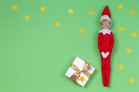 Christmas background. Toy elf and white present box with ribbon on light green background 写真素材
