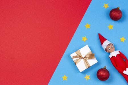 Christmas background. Xmas present, decoration and toy elf on red and blue background 写真素材