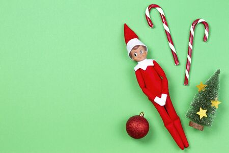Christmas background. Toy elf, candy canes, little Xmas tree with red bauble on light green background. Top view