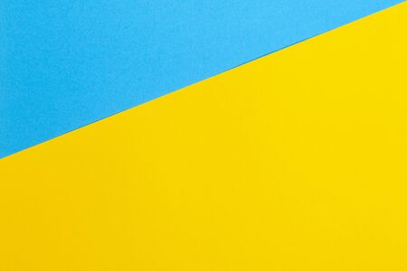 Color papers geometry flat composition background with yellow and blue tones