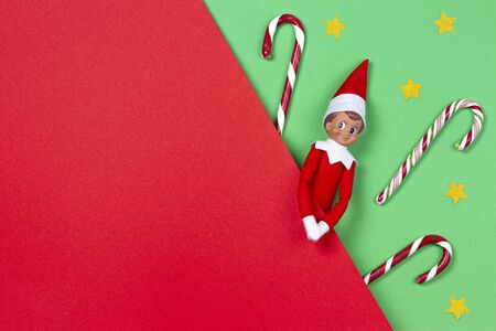 Christmas background. Toy elf, candy canes, littlegoolden stairs on red and green background. Top view Banco de Imagens