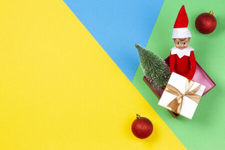 Christmas background. Xmas present, decoration and toy elf on yellow, green and blue background 写真素材