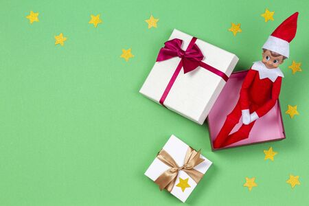 Christmas background. Xmas present boxes and toy elf on light green background. Top view 写真素材