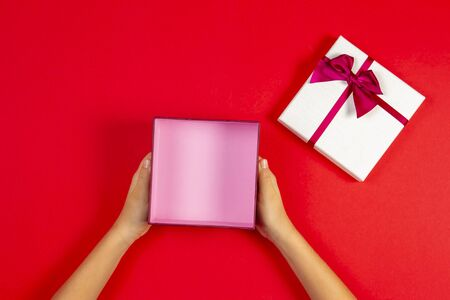 Present box template mock up. Hand open empty present gift box on pastel pink background, top view 写真素材