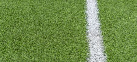 Green artificial grass soccer sports field with white stripe line
