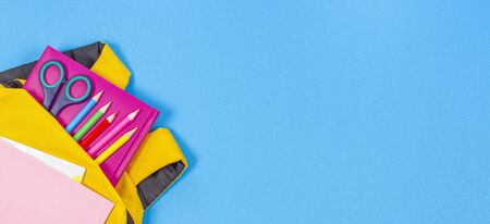 Back to school concept. Yellow backpack with school supplies on light blue background. Top view