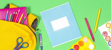 Back to school concept. Yellow backpack with school supplies and notebook on green background. Top view 写真素材