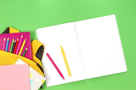 Back to school concept. Backpack with school supplies and open paper notebook on green background. Top view 写真素材
