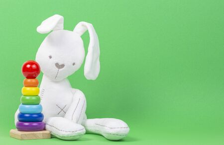 White plush toy rabbit with wooden baby stacking rings pyramid on light green background