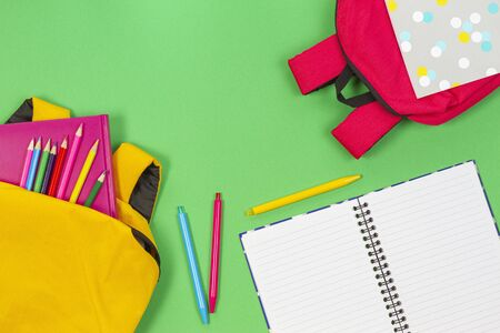 Back to school concept. Yellow and pink backpacks with school supplies, books and notebooks on light green background. Top view 写真素材