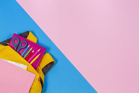 Back to school concept. Yellow backpack with school supplies on pastel pink and light blue background. Top view 写真素材