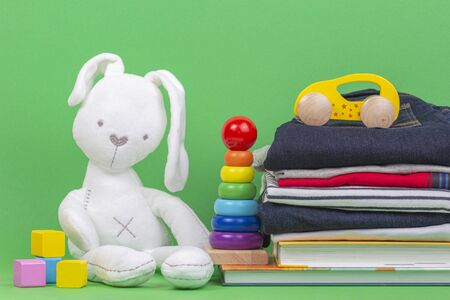 Donation concept. Kid toys, books and clothes for donate or charity on green background