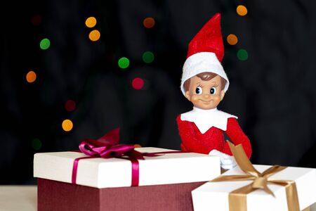 Christmas toy elf and present gift boxes with christmas tree background