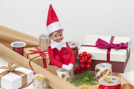 Christmas present wrapping background. Gifts present boxes, wrapping papers, ribbons, bows and toy elf on white table