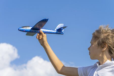 Kid playing with blue toy plane against blue sky